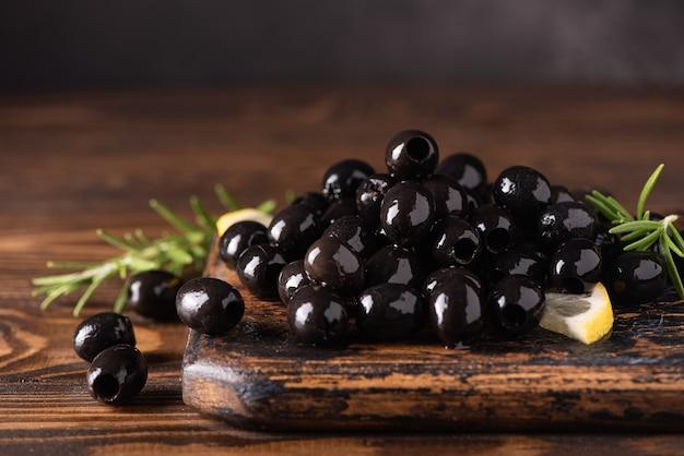 Entkernte schwarze oliven auf holzbrett, nahaufnahme