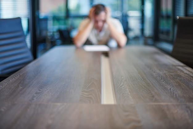 Entlassener angestellter im konferenzraum. manager bei tisch im modernen konferenzzimmer für geschäftsverhandlungen und geschäftstreffen.
