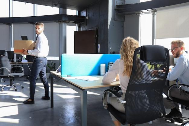 Entlassener arbeiter, der mit seinem büromaterial aus dem büro geht.