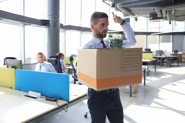 Entlassener arbeiter, der mit seinen büroartikeln aus dem büro geht und fick zeigt.