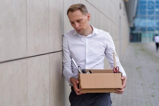 Entlassener büroangestellter hält eine schachtel mit seinem briefpapier in der hand. nahansicht. freier platz.