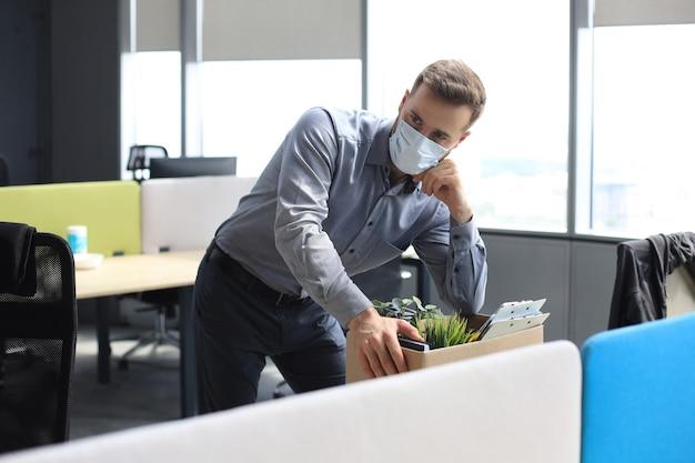 Entlassung mitarbeiter in einem epidemischen coronavirus covid-19. trauriger entlassener arbeiter nimmt seine büromaterialien aus dem büro mit