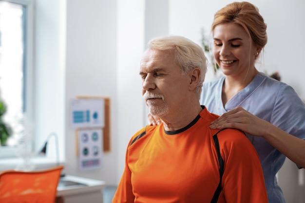 Entlastung für die muskulatur. angenehmer älterer mann, der lächelt, während er seine schultermassage genießt