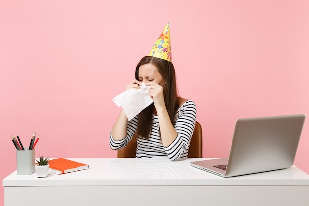 Entnervte frau mit partyhut, die tränen mit taschentuch abwischt, weil sie allein im büro am weißen schreibtisch mit laptop geburtstag feiert