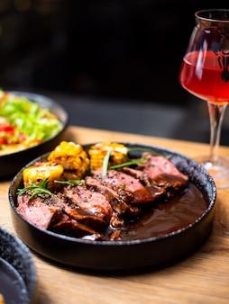 Entrecote beef gegrilltes steakfleisch mit feuerflammen auf holzbrett mit rosmarinzweig, pfeffer und salz. gegrilltes gemüse, mais. meisterkoch, der köstlichen grillgrill kocht.