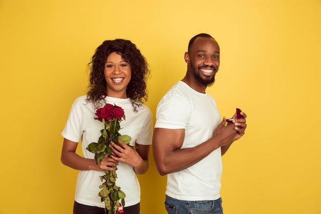 Entscheidung. valentinstagfeier, glückliches afroamerikanisches paar lokalisiert auf gelber wand. konzept der menschlichen gefühle, gesichtsausdruck, liebe, beziehungen, romantische feiertage.