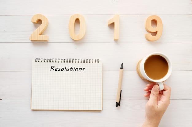 Entschließung 2019 auf leerem notizbuchpapier und -hand, die kaffeetasse hält