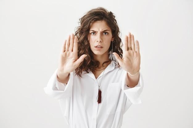 Entschlossene ernsthafte frau, die eine stoppgeste zeigt und ihre hände ausstreckt, um handlungen zu verbieten