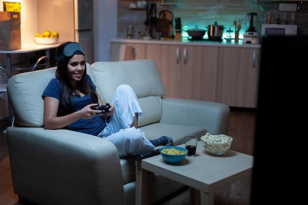 Entschlossene frau, die nachts ein videospiel im wohnzimmer spielt