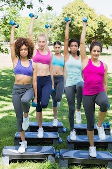 Entschlossene frauen, die stepp-aerobic im park tun