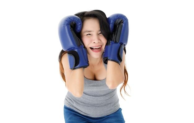 Entschlossene junge fitte asiatische frau in blauen boxhandschuhen, die in kampfhaltung steht und mit einem lächeln auf weißem hintergrund in die kamera schaut