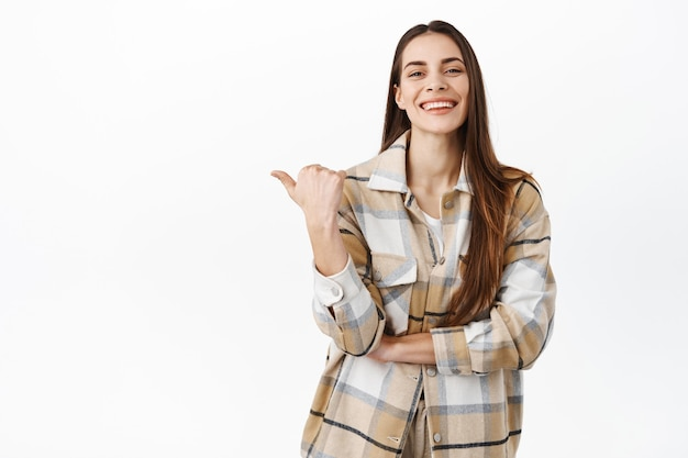 Entschlossene lächelnde frau, die beiseite auf exemplar zeigt, das logo auf der linken seite zeigt und vorne zufrieden und glücklich aussieht, über weißer wand stehend