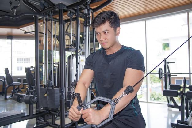 Entschlossener asiatischer mann, der pecs auf turnhallenausrüstung ausübt
