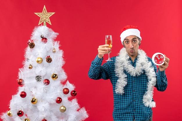 Entschlossener emotionaler junger mann mit weihnachtsmannhut und hält ein glas wein und uhr nahe weihnachtsbaum auf rot