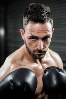 Entschlossener hemdloser mann mit boxhandschuhen an der crossfit turnhalle