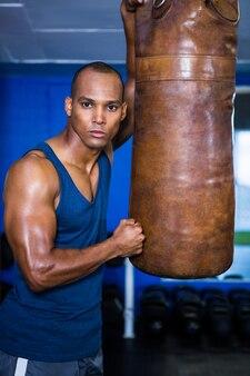 Entschlossener junger mann, der durch boxsack steht