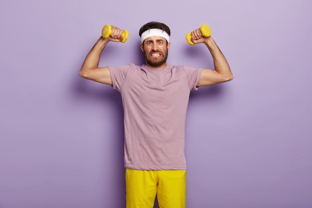 Entschlossener junger sportlicher unrasierter mann beißt die zähne zusammen, hebt die muskulösen arme an, macht übungen mit hanteln, beißt die zähne zusammen