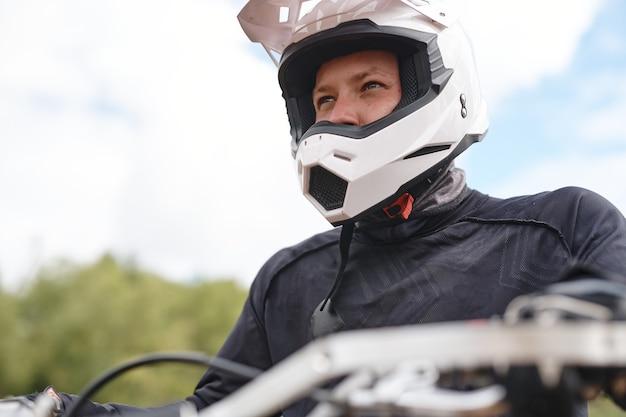 Entschlossener motorradfahrer in weißem helm und jacke, der auf dem motorrad sitzt und im freien in die ferne schaut