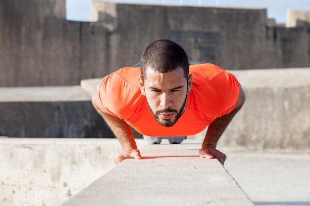 Entschlossener sportlicher mann, der push-ups auf parapet tut