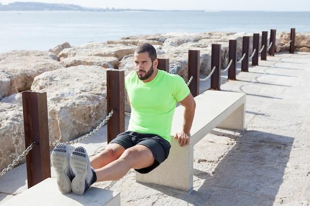 Entschlossener sportlicher mann, der trizeps-dips auf bänken tut