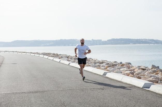 Entschlossener starker sportler, der am meer läuft