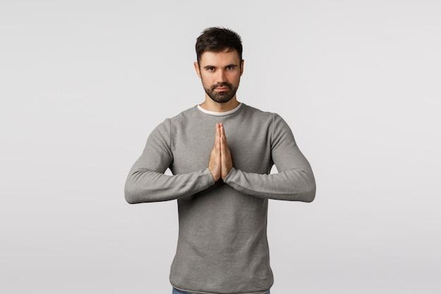 Entschlossener und motivierter schöner bärtiger kaukasischer kerl in der grauen strickjacke, höflich beugend mit den händen zusammengedrückt im namaste, asiatischer gruß, lächelnd und beten