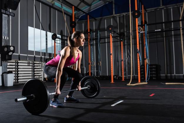 Entschlossenes sportliches mädchen trainiert im fitnessstudio mit einer langhantel