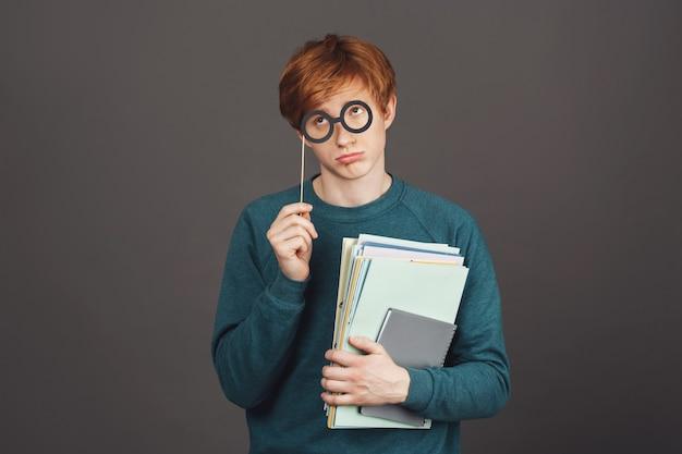 Entschuldigen sie, miss, ich werde das nächste mal ein guter junge sein. gut aussehender lustiger junger männlicher student im bequemen grünen sweatshirt, das papiere hält und mit schuldigem blick durch papiergläser beiseite schaut.