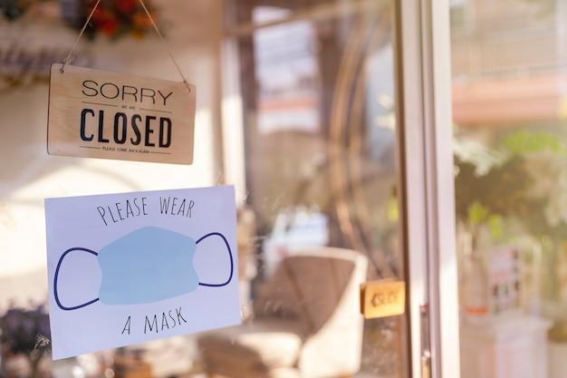 Entschuldigung, wir haben geschlossenes holzschild und bitte tragen sie eine gesichtsmaske, bevor sie das papier an der glastür betreten
