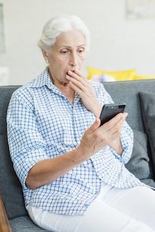 Entsetzte ältere frau, die smartphone betrachtet