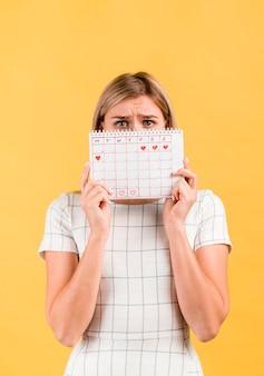Entsetzte frau, die ihr gesicht mit zeitraumkalender bedeckt