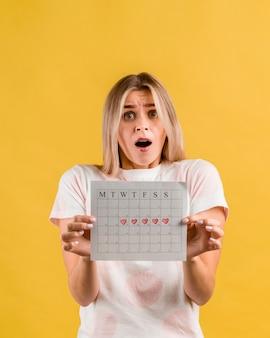 Entsetzte frau, die ihre vorderansicht des zeitraumkalenders zeigt