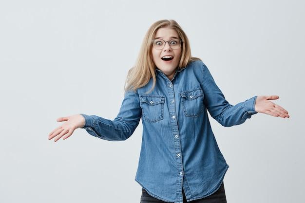 Entsetzte frau mit blonden haaren und brillen gestikuliert verwirrt, schockiert und überrascht, als sie sich daran erinnert, dass sie vergessen hat, rechnungen zu bezahlen. frustrierte frau mit abgehörten augen ruft in panik aus