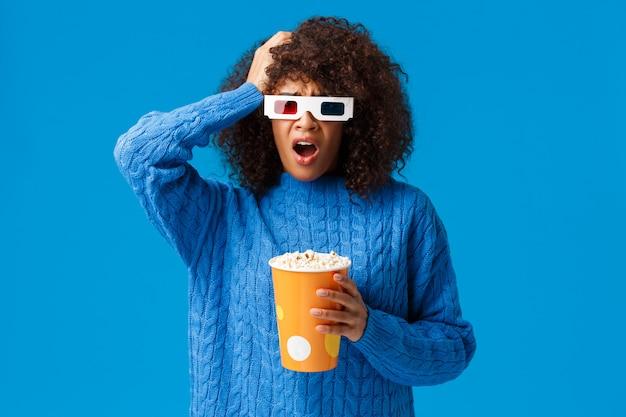 Entsetzte hübsche frau des afroamerikaners betroffen mit dem entsetzen des cliffhanger im film, ergreifen den unruhigen und verärgerten kopf und lassen den kiefer fallen und halten den aufpassenden film des popcorns im kino, blau