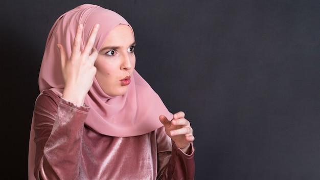Entsetzte islamische frau, die gegen schwarzen hintergrund steht