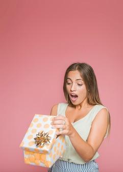 Entsetzte junge Frau, die Blumengeschenkbox gegen rosa Hintergrund öffnet