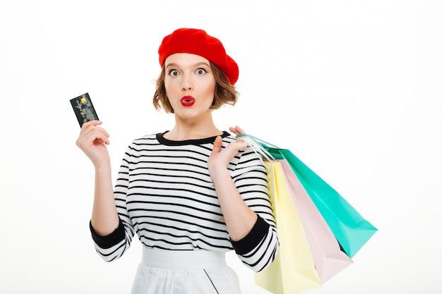 Entsetzte junge frau, die kreditkarte und einkaufstaschen hält