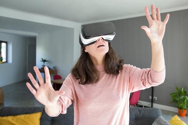 Entsetzte junge frau, die welt im kopfhörer der virtuellen realität lernt