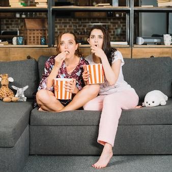 Entsetzte junge frauen, die auf dem aufpassendem fernsehen des sofas sitzen