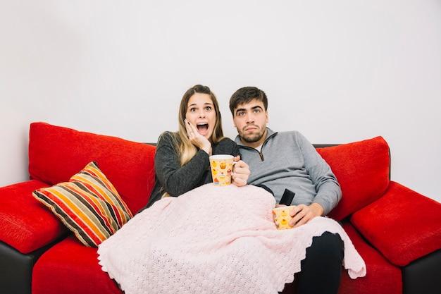 Entsetzte paare, die auf aufpassendem film des sofas sitzen