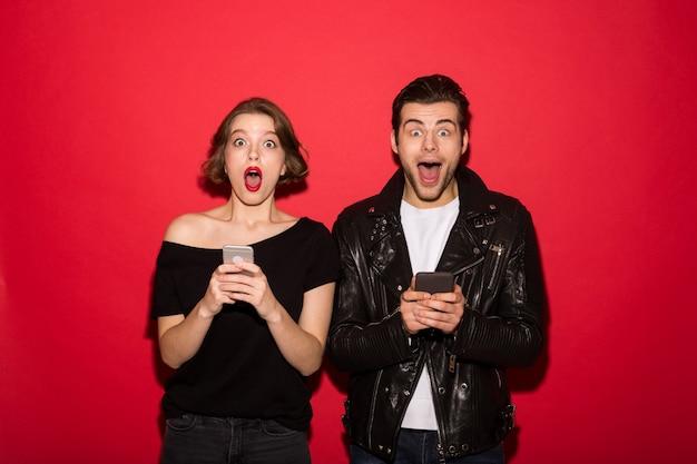 Entsetzte punkpaare, die ihre smartphones beim schauen halten