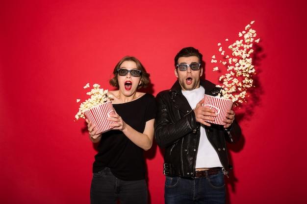 Entsetzte punkpaare zerstreuen popcorn und das schauen