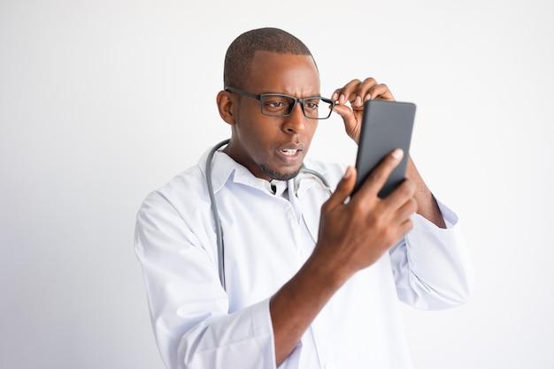Entsetzte schwarze männliche doktor-lesenachrichten auf smartphone.