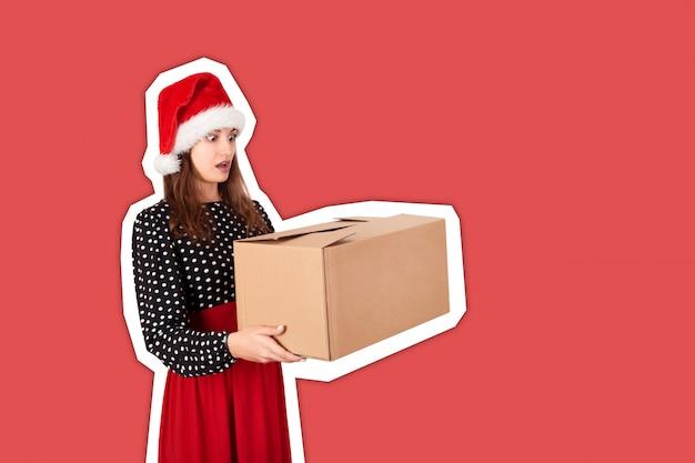 Entsetzte und überraschte recht junge frau, die große kartongeschenkbox hält. magazin-collage-stil
