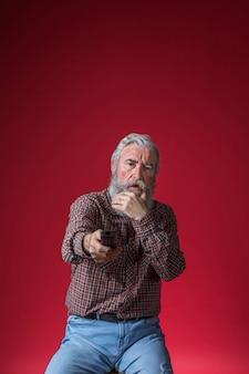 Entsetzter älterer mann, der den kanal des fernsehens mit fernbedienung gegen roten hintergrund ändert