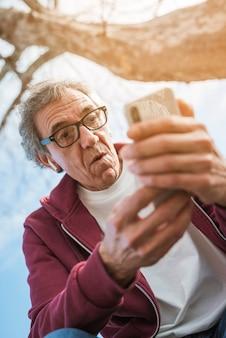 Entsetzter älterer mann, der unter dem baum betrachtet intelligentes telefon sitzt