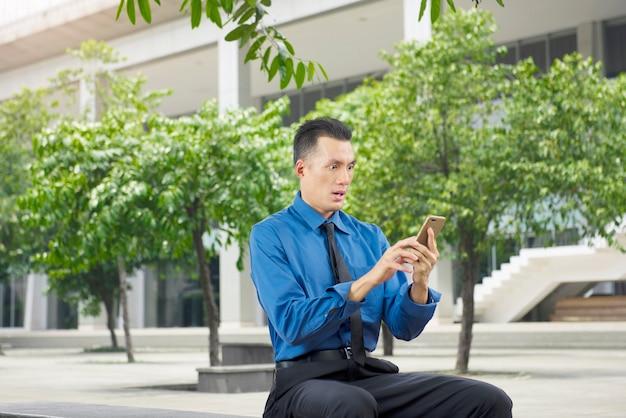 Entsetzter asiatischer geschäftsmann, nachdem etwas an seinem telefon geschaut worden ist