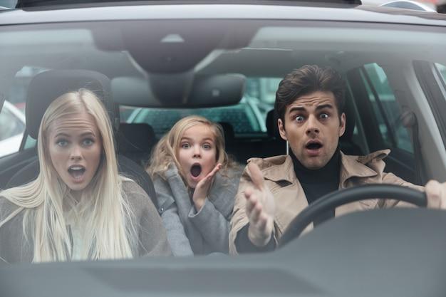 Entsetzter erschrockener junger mann, der im auto mit familie sitzt