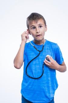 Entsetzter junge, der auf seinen herzschlag mit stethoskop auf weißem hintergrund hört