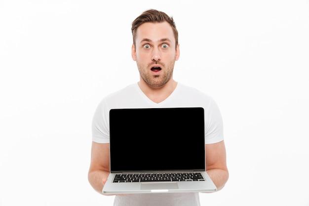 Entsetzter junger mann, der anzeige des laptops zeigt.